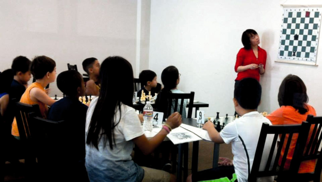Kwunnie Ng (far right) providing valuable instruction to future Grand Masters at Chess 64 in Houston.  Kwunnie Ng is a Senior Tournament Director and FIDE National Arbiter.  She is the owner of The Chess Refinery, a pending 501(c)(3) in Houston.  Photo from the Chess 64 Facebook page.