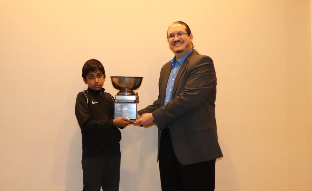 """Chess Expert Vasee Nandhakumar (wearing the """"Niki Swoosh"""") receives his State Amateur Champion title and trophy from Chief Arbiter Louis Reed. Photo by Arlington Chess Club's Jim Clarke."""